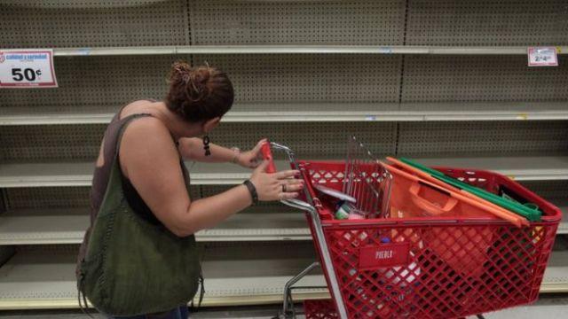 Una mujer mira un estante vacío en una tienda de San Juan