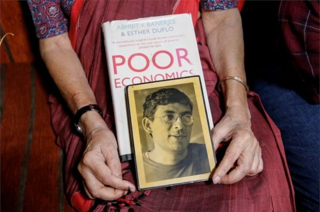 Nirmala Banerjee, mother of Abhijit Banerjee, one of the winners of 2019 Nobel Economics Prize, holds his portrait and one of his books, as she speaks to media at her house in Kolkata, India, October 14, 2019.