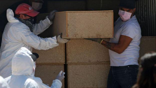 Trabajadores forenses descargan los ataúdes de víctimas no identificadas de la violencia en Ciudad Juárez, Chihuahua