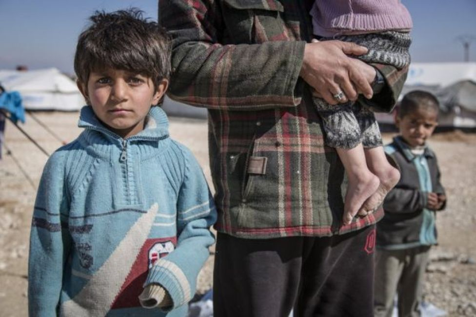 A boy, 7, looks at the camera at a refugee camp in Syria. He stands next to his father, Hisham (not his real name), who carries an infant. We cannot see either of their faces. Another child looks on from behind.
