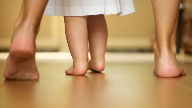 Una madre y su beba caminando descalzas en una casa