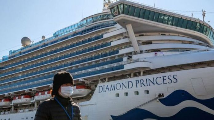 A person wearing a mask walks in front of a large cruise ship