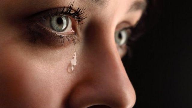 Le visage d'une femme avec une larme sur la joue