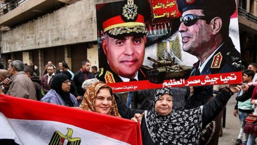 Egyptian women hold their national flag and a poster bearing portraits of President Abdul Fattah al-Sisi (R) and Defence Minister Sedki Sobhi in Tahrir Square, on the sixth anniversary of the 2011 uprising that ousted Hosni Mubarak (25 January 2017)