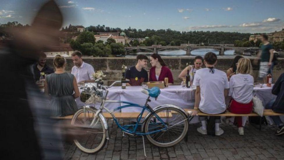Un couple assis à une table sur le pont Charles à Prague