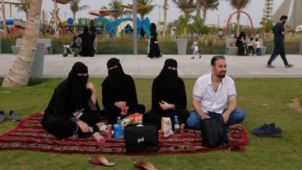 Tres mujeres completamente cubiertas de negro en Arabia Saudita, acompañadas de un hombre.