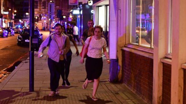 La gente correre giù Borough High Street, mentre la polizia che fare con una