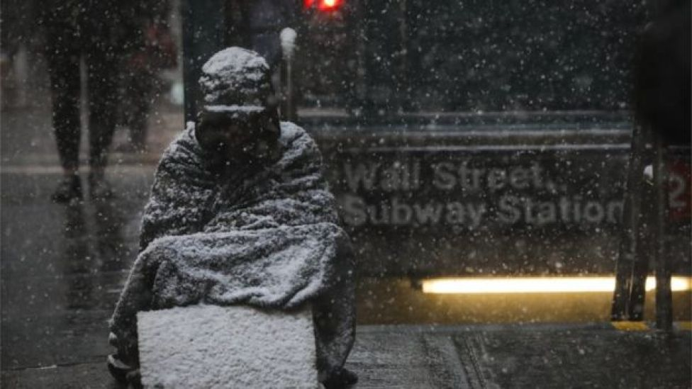 Homeless individual sits outside NYC subway station