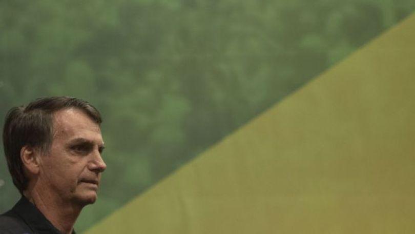 Jair Bolsonaro de perfil em frente a bandeira do Brasil