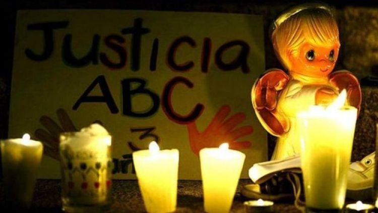 """Una muñeca con un cartel que dice """"Justicia ABC"""""""