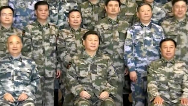 Chinese President Xi Jinping, in military uniform, poses for a group photo with military staff members at the Chinese army's Joint Operation Command Centre in Beijing, 21 April 2016