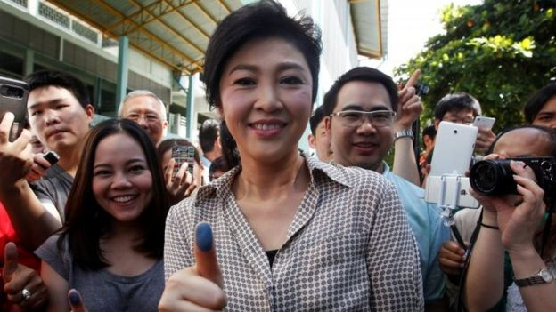Former Thai Prime Minister Yingluck Shinawatra (centre) shows her inked finger after casting her vote in Bangkok