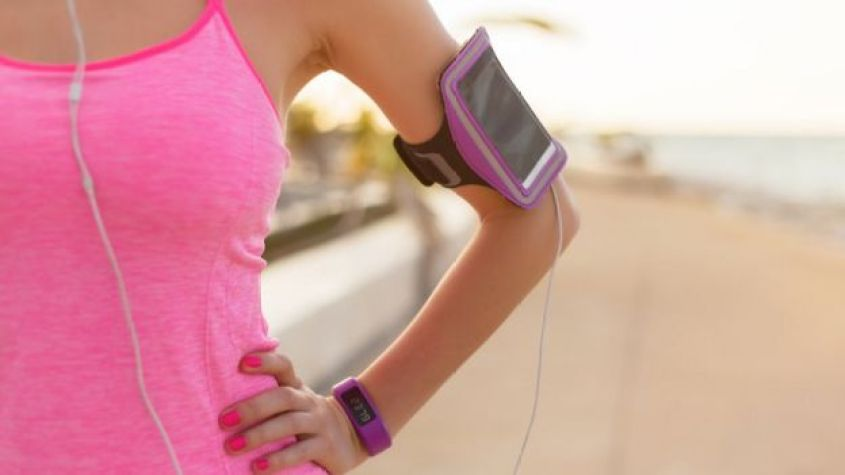 Woman with smartphone and fitness watch