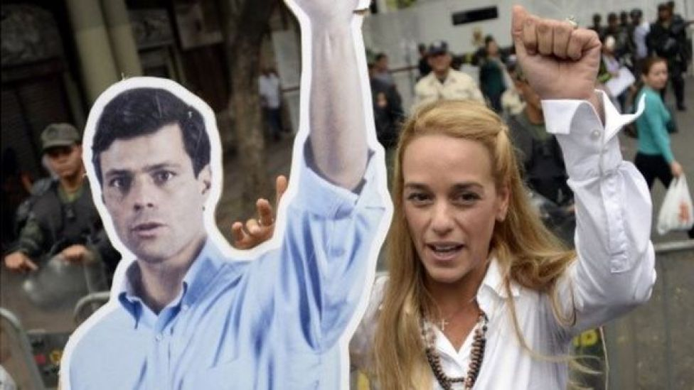 The wife of arrested opposition leader Leopoldo Lopez, Lilian Tintori, raises her fist next to a poster of her husband in front of the Venezuelan courthouse in Caracas on July 23, 2014.