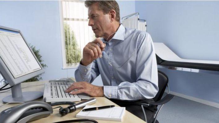 طبيب يراجع حالة أحد المرضي على الحاسوب