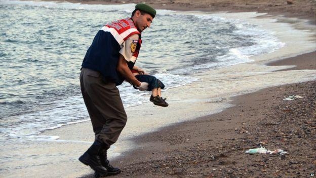 A paramilitary police officer carries the lifeless body of a migrant near the Turkish resort of Bodrum - 2 September 2015