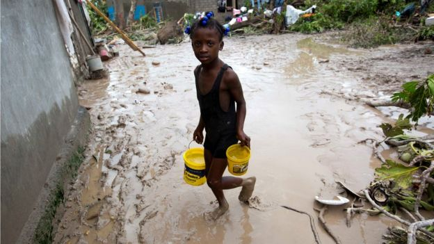 A girl lugs buckets of drinking water after the passing of Hurricane Matthew in Les Cayes, Haiti, 6 October