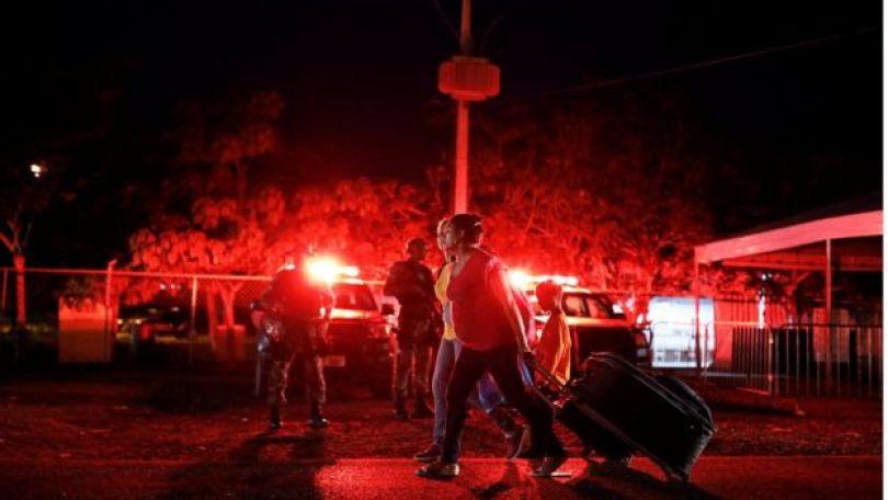 Militares fazem patrulha enquanto venezuelanas caminham em direção a Santa Elena para dormir depois de terem passado pela fronteira em Pacaraima