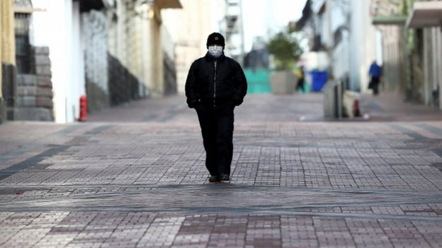 Un hombre camina por el centro de Quito.