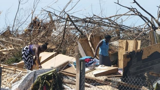 Two women look through the remains of a house destroyed by Hurricane Dorian in Great Abaco Island, Bahamas, 5 September