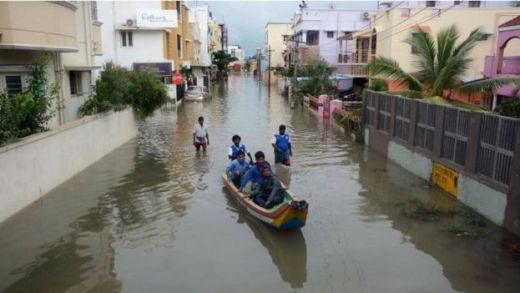 Indian people make their way in a canoe on a flooded street following heavy rain in Chennai on November 16, 2015.