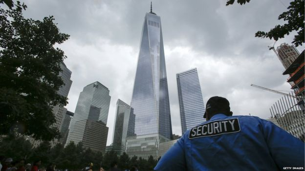 Security worker keeps an eye on tourists at Ground Zero and One World Trade Center on 4 July, 2015