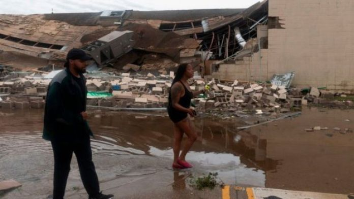 Dos personas pasan delante de un edificio destruido tras el paso del huracán Laura.