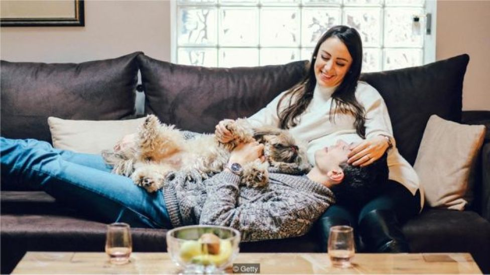 Casal no sofá com cachorro