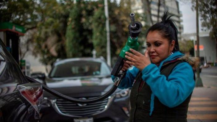Trabajadora de gasolinera reponiendo combustible.
