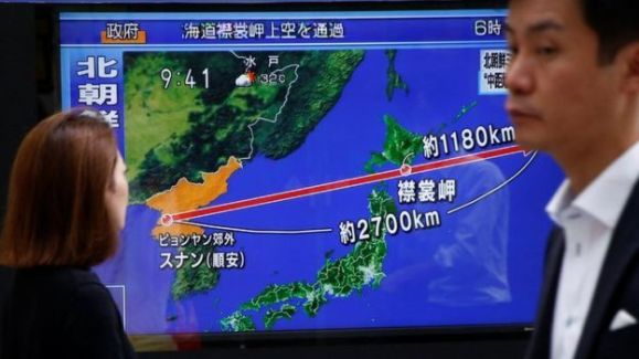 Pessoas olham uma TV que traz noticiário em japonês sobre o míssil norte-coreano