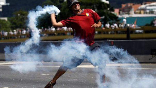 Un manifestante con una bomba de humo