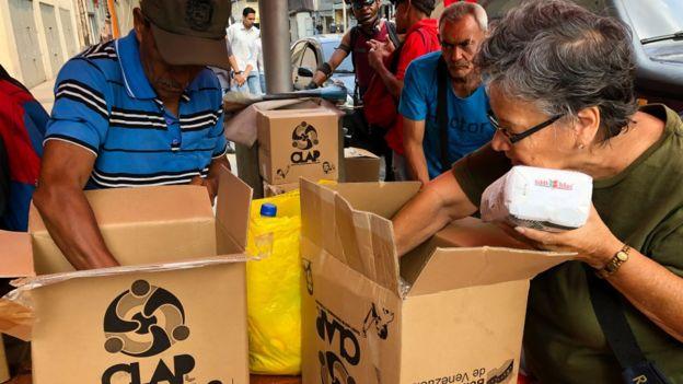Venezuelanos abrindo caixas CLAP.