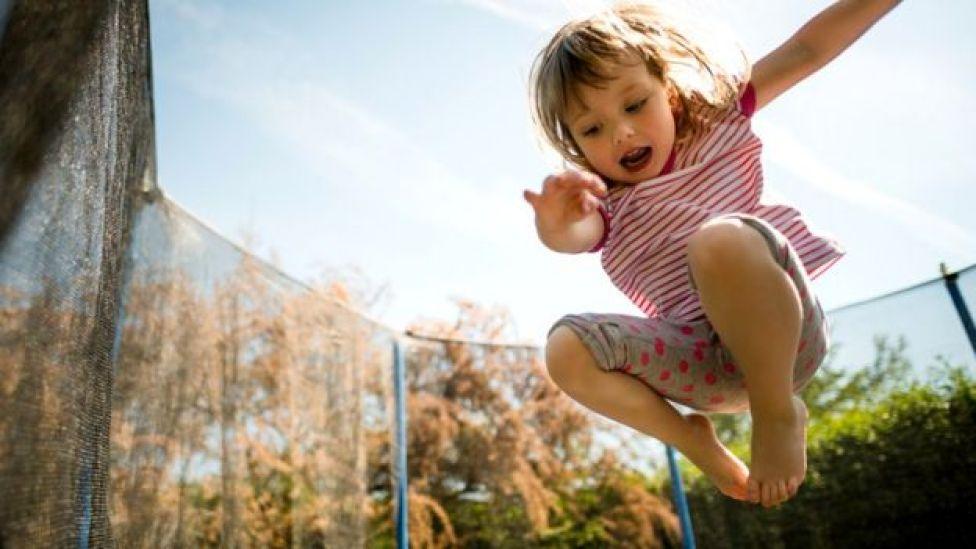 Niña saltando en una colchoneta  Qué tipo de deporte es mejor para estar sano según tu edad  105551434 salto