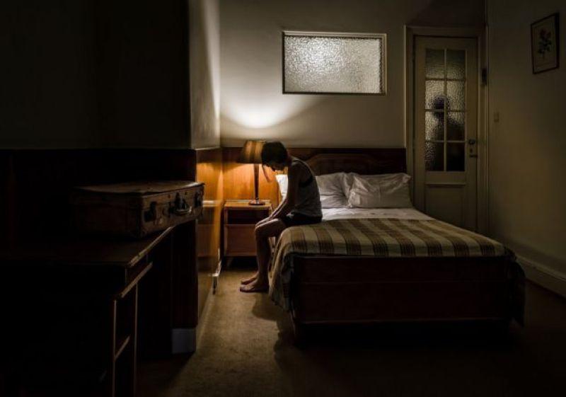 Mulher sentada em sua cama olhando para baixo