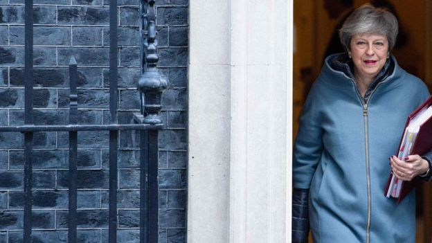 Theresa May, carrying a red folder, leaves the door of 10 Downing Street