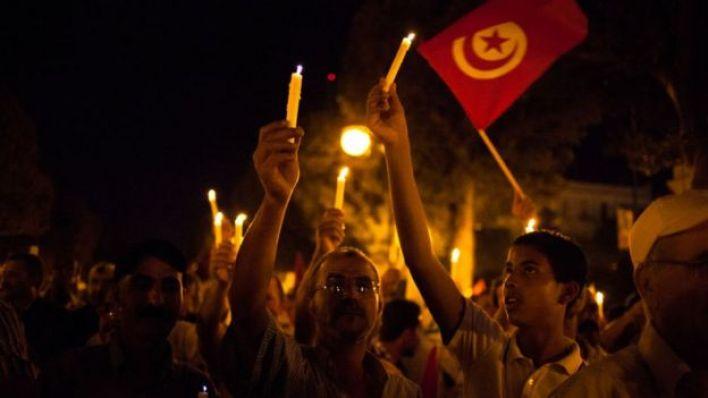 متظاهرون يحملون الشموع والعلم التونسي (أرشيفية)