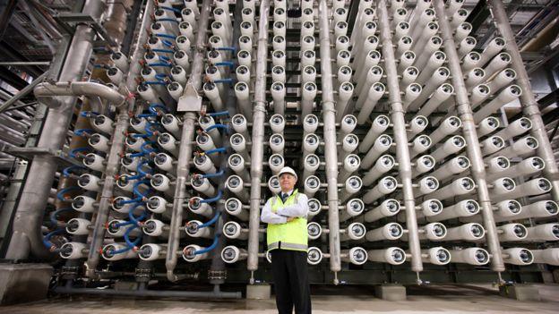 Ingeniero frente a tubos con membranas para filtrar el agua marina en una planta desalinizadora