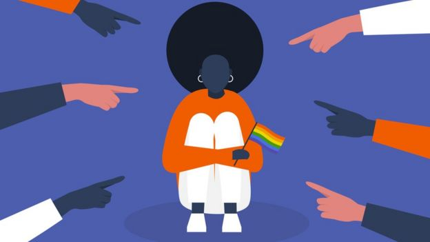 Person of colour holds a Pride flag and is pointed at