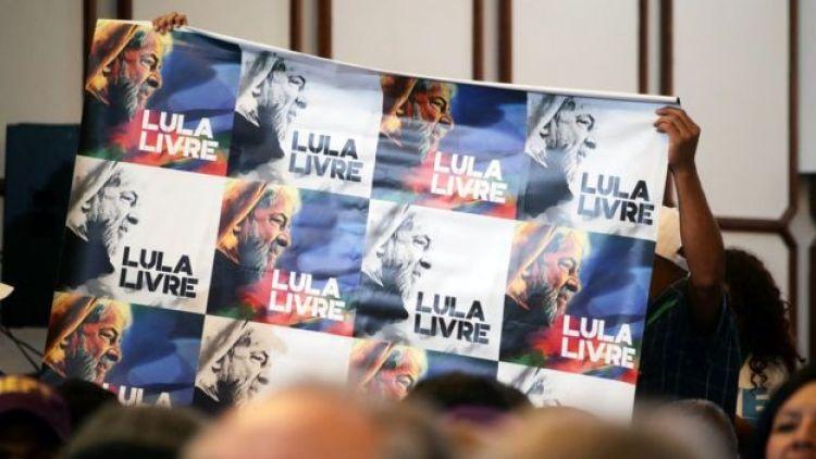 Em meio a plateia em evento, cartaz é levantado com diversas fotos de Lula e dizeres 'Lula Livre'
