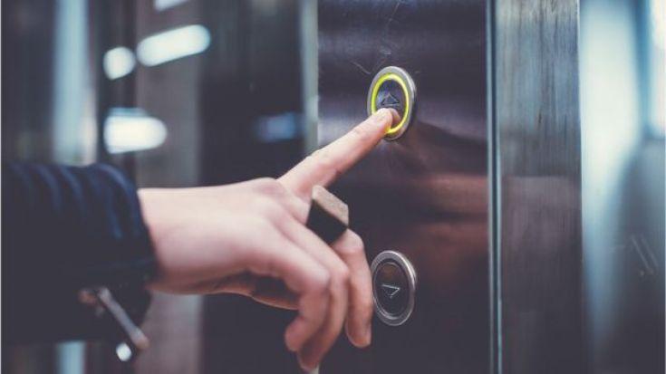 Mujer oprimiendo el botón del ascensor