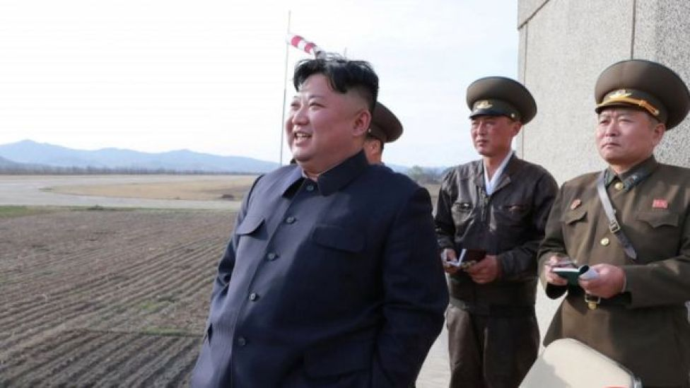 Kim Jong-un watches a flight training on April 16 with military personnel assisting him