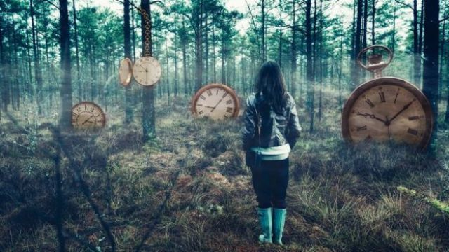 Concept of time and choosing your right path: there's a woman standing in the middle of a foggy forest, with big clocks scattered all around.