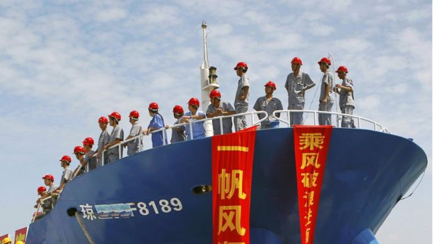 Uniformed staff in red helmets, standing on a fishing vessel setting sail for the Spratly Islands, draped with red and yellow flags on which are written slogans in Chinese, on 6 May 2013.