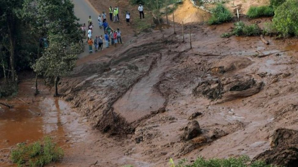 Residents are seen in an area next to a dam that burst