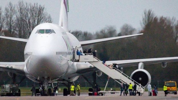 Passengers disembark a plane from Wuhan