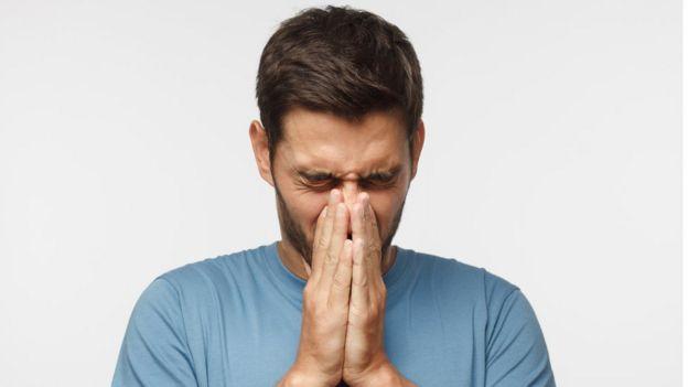 Hombre joven agarrándose la nariz en señal de dolor.