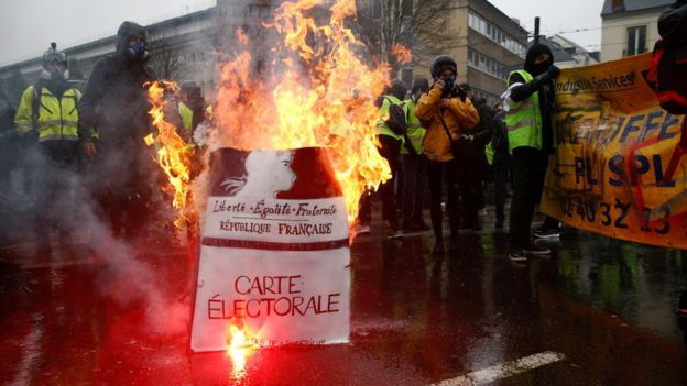 """Protesters wearing yellow vests stand near a burning facsimile voter registration card during a demonstration by the """"yellow vests"""" movement in Nantes, France, 15 December."""
