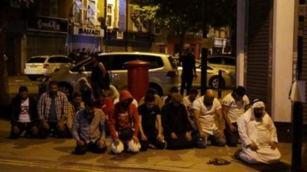 Muslim men pray on the street in the aftermath of the van attack