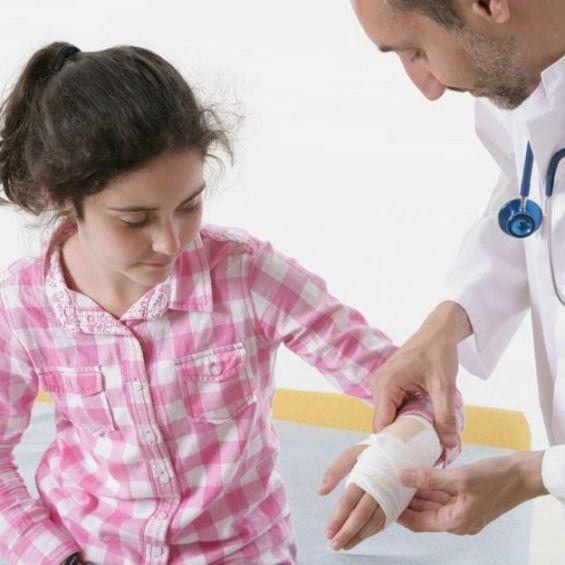 Médico atendiendo a una niña que tiene la muñeca enyesada