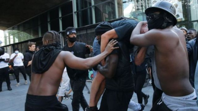 Amigos protegem Hutchinson, que carrega um manifestante branco